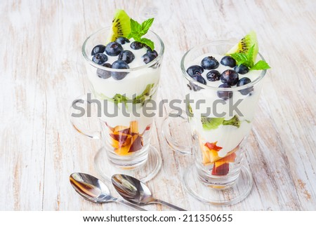 Fresh fruit in cream. A dessert from fruit and cream - stock photo