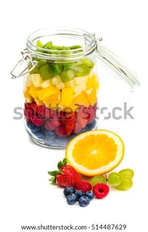 Fresh fruit in front of glass jar full of colorful fruits on white background