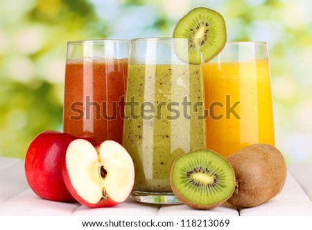 fresh fruit juices on wooden table, on green background - stock photo