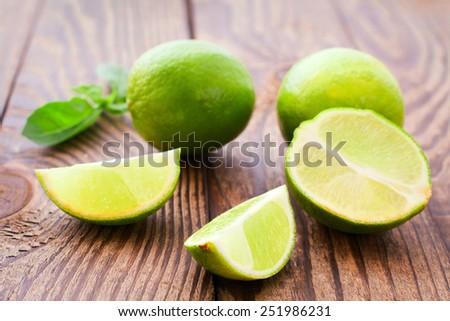 Fresh fruit limes on wooden background closeup horizontal - stock photo