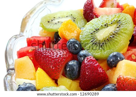 Fresh fruit salad in a crystal bowl.  Luscious healthy eating, with kiwi fruit, strawberries, blueberries, canteloupe, watermelon, mango, oranges, and passionfruit - stock photo