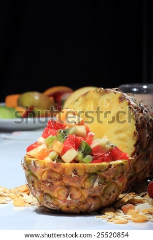 Fresh fruit salad in a pineapple on dark background