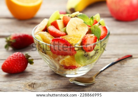 Fresh fruit salad in bowl on grey wooden background - stock photo