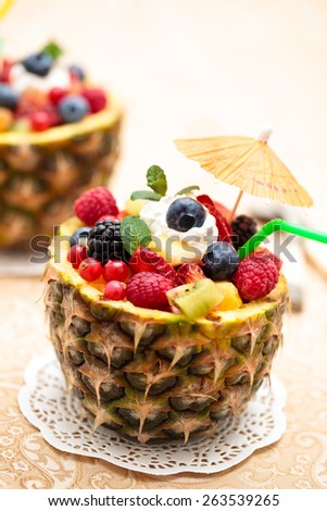 Fresh fruit salad in pineapple  bowl with kiwi, orange, berries and mint leaf ( Focus on part of mint leaf and on berries next to it). - stock photo