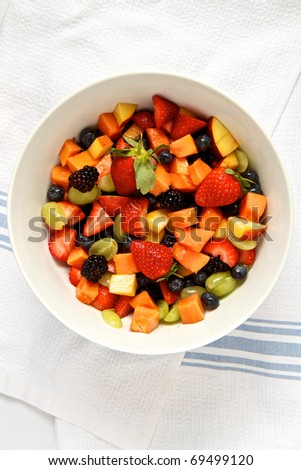Fresh fruit salad in white bowl against cloth background - stock photo