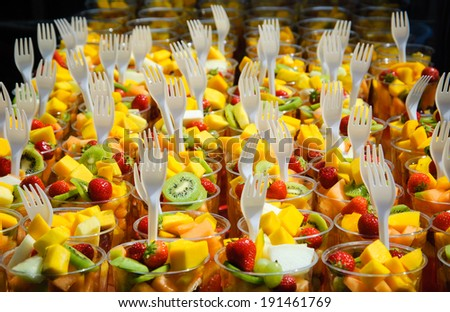 Fresh fruit salad (kiwi, mango, strawberry etc.) arranged in plastic cups with forks on a market stall. Selected focus. Healthy fast food concept. - stock photo