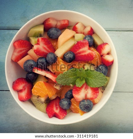 Fresh fruit salad on wood table - stock photo