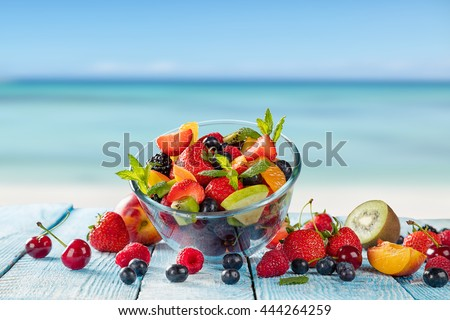 Fresh fruit salad placed on wooden planks, blur sea on background. Concept of healthy eating, antioxidants and summer time. - stock photo