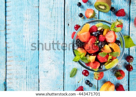 Fresh fruit salad with various kind of berry and citrus fruit served in glass bowl, placed on wooden table. Shot from aerial view, copyspace for text - stock photo