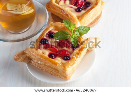 Fresh fruit tart with berries jam decorated with cranberry, mint on wooden rustic background wit a cup of tea. Desert. Morning healthy breakfast and evening dinner.