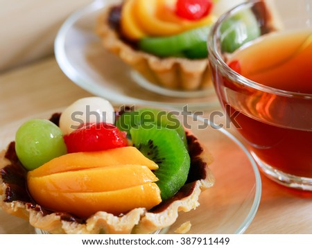 fresh fruit tarts on wooden panel include kiwi, lychee,grapefruit, strawburry,peaches and a cup of herbal tea on wooden table
