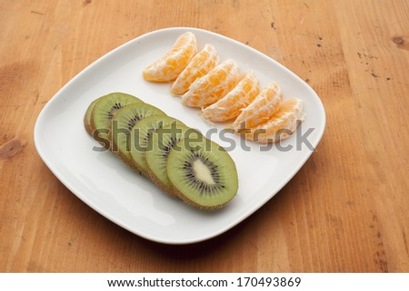 fresh fruit with kiwi and tangerines on white plate. Healthy eating. - stock photo