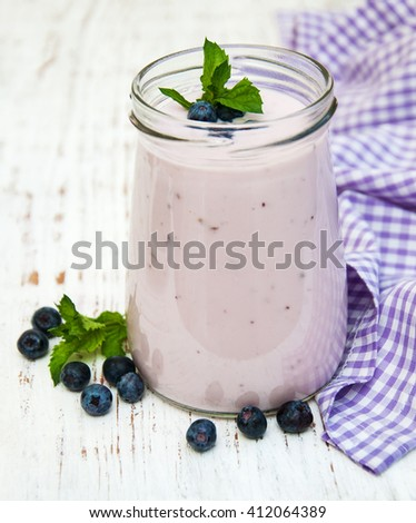 fresh fruit yogurt with blueberries on a wooden background