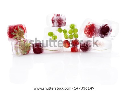Fresh fruits and vegetable frozen in ice cubes isolated on white background. Fresh summer eating.  - stock photo