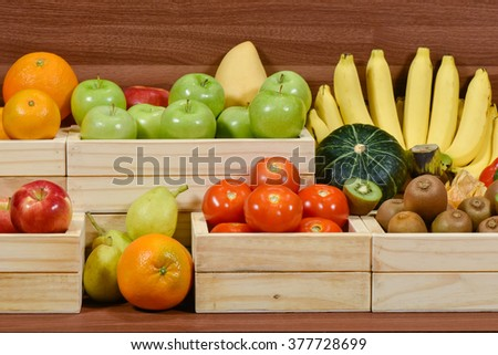 Fresh fruits and vegetables in woodem box at the supermarket - stock photo