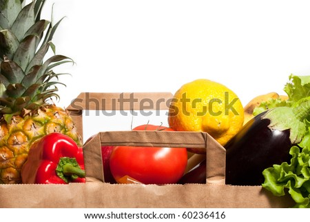 Fresh fruits and vegetables inside a paper bag on white background - stock photo