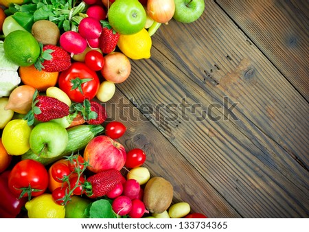 Fresh fruits and vegetables on the old wooden board - stock photo