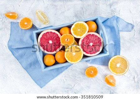 Fresh fruits citruses on a rustic white background. Raw and vegetarian eating frame. Sliced tangerines, oranges, grapefruits on a blue tray.  Fruit set. Top view - stock photo