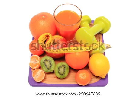 Fresh fruits, dumbbells for using in fitness, tape measure and glass of juice, concept for slimming, healthy nutrition and strengthening immunity - stock photo