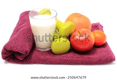 Fresh fruits, glass of milk and green dumbbells for using in fitness lying on purple towel, concept for healthy nutrition and lifestyle - stock photo