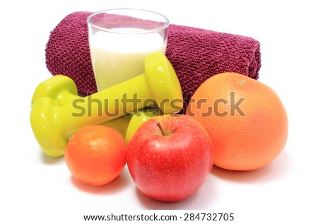 Fresh fruits, glass of milk, green dumbbells and purple towel for using in fitness, concept for healthy nutrition and lifestyle