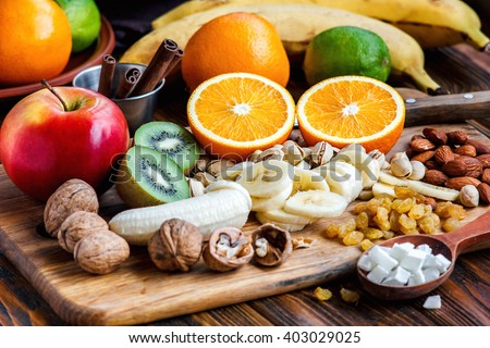 Fresh fruits. Healthy food. Mixed fruits and nuts background.Healthy eating, dieting, love fruits. Studio photography of different fruits and nuts on old wooden table. Organic Healthy Assorted Fruits. - stock photo