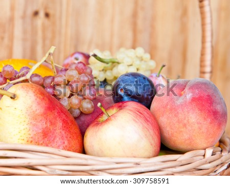 Fresh fruits in a basket against wooden wall - stock photo