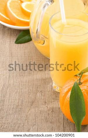 fresh fruits juice in glass and orange on wood background - stock photo