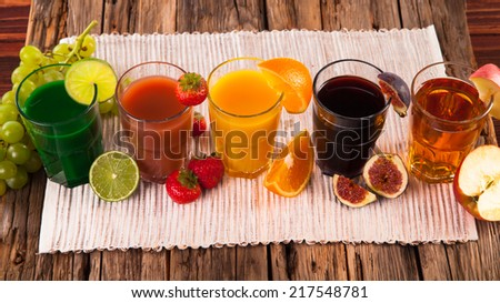 Fresh fruits juices on wood plant, strawberry, orange, lime, ficus and apple drinks  - stock photo
