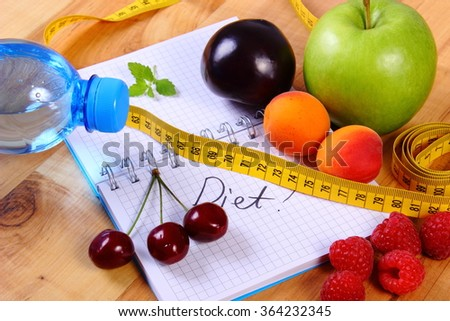 Fresh fruits, mineral water and tape measure with notebook for writing notes, concept of slimming, diet and healthy nutrition - stock photo