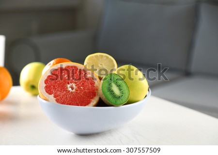 Fresh fruits on table in living room, close up - stock photo