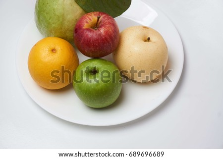 Fresh fruits on white plate isolated on white background. Selective focus.