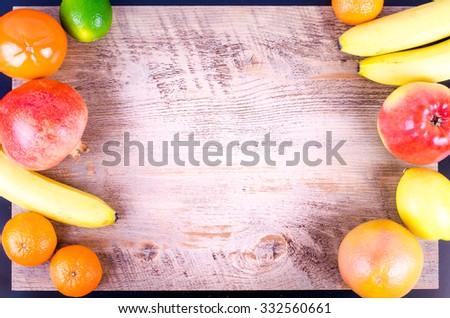Fresh fruits on wooden background. Summer background. Raw and vegetarian eating background. Lemon, apple,  grapefruit, pomegranate, lime, persimmon, tangerine, orange, banana. Top view - stock photo
