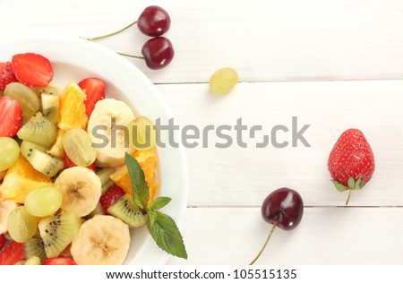 Fresh fruits salad on plate and berries on white wooden table - stock photo