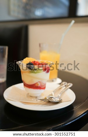 Fresh fruits salad with ice cream in glass on table