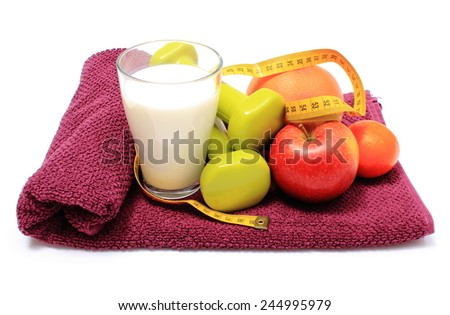 Fresh fruits, tape measure, glass of milk and green dumbbells for using in fitness lying on purple towel, concept for slimming, healthy nutrition and lifestyle - stock photo
