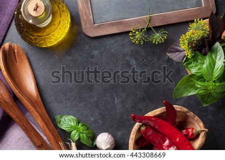 Fresh garden herbs in mortar, chili pepper and olive oil on stone table. Basil, rosemary, dill. Cooking ingredients. Top view with copy space - stock photo