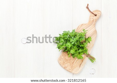Fresh garden parsley on cutting board. Top view with copy space - stock photo