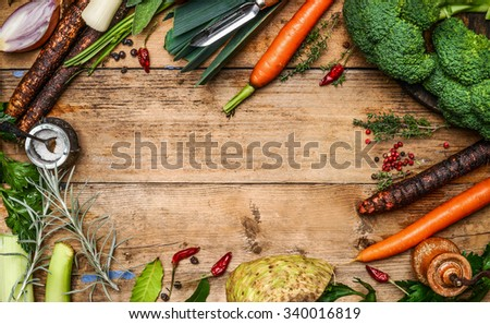 Fresh garden vegetables ingredients for broth or soup cooking on rustic wooden background, top view. Healthy eating concept - stock photo