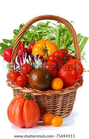 Fresh garden vegetables with water drops on a wicker basket. - stock photo