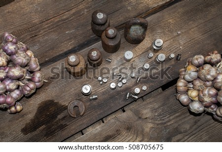 Fresh garlic and weights on a wooden table top