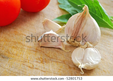 Fresh garlic cloves on chopping board with vegetables. Commonly used as seasoning and food ingredient in many Chinese cuisine. For food and beverage concepts. - stock photo