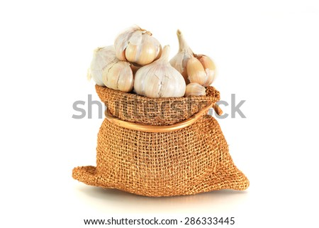 Fresh garlic in bag on white background  - stock photo