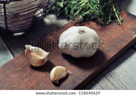 Fresh garlic on cutting board on vintage wooden background - stock photo