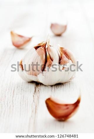 Fresh garlic on white wooden table, selective focus - stock photo