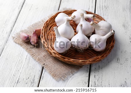 Fresh garlic on wicker mat, on wooden background - stock photo