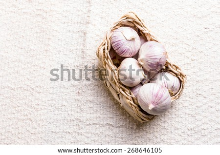 Fresh garlics in woven basket, nice background - stock photo