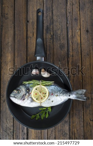 Fresh gilt-head sea bream fish with herbs and spices on a pan ready to be cooked - stock photo