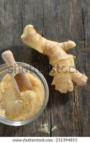 Fresh ginger root with a spicy powder in bowl, wooden background - stock photo