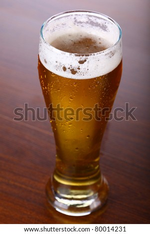 fresh glass of beer on wooden background - stock photo